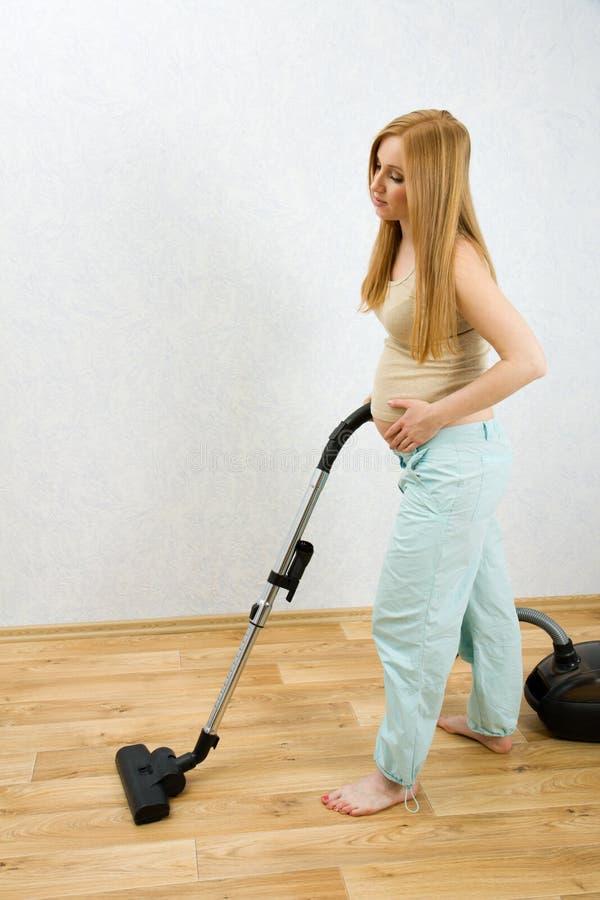 Reinigungsfußboden der schwangeren Frau mit Staubsauger lizenzfreie stockbilder