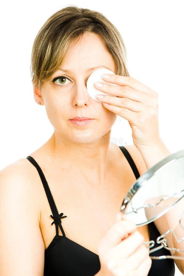 Reinigungsgesicht der blonden mittleren Greisin mit Baumwollauflage - Hautpflege an irgendeinem Alter - Abdeckung von einem Auge lizenzfreies stockbild