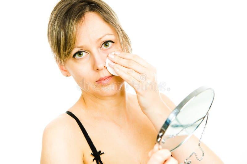 Reinigungsgesicht der blonden mittleren Greisin mit Baumwollauflage - Hautpflege stockbild