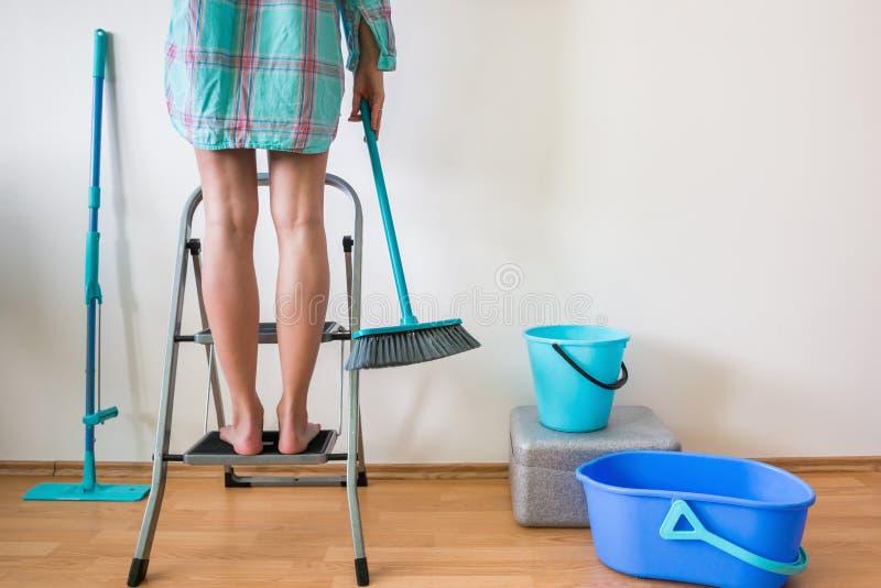 Reinigungshaus der jungen Frau mit Leiter und Bürste stockfotografie
