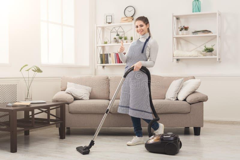Reinigungshaus der jungen Frau mit Staubsauger stockfotos