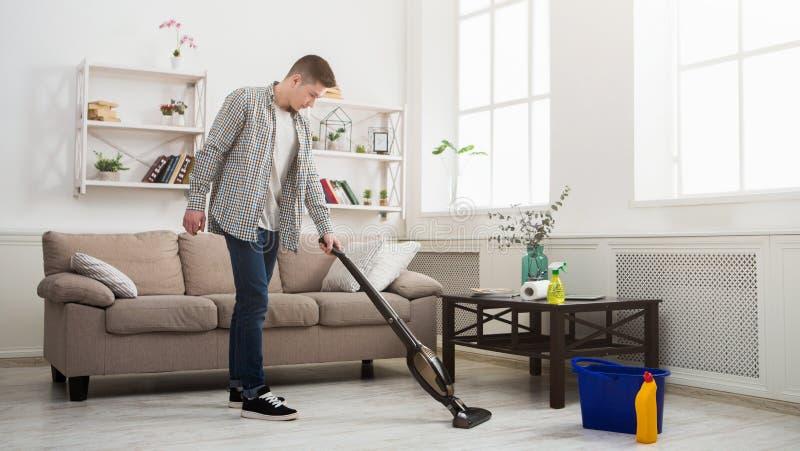 Reinigungshaus des jungen Mannes mit Staubsauger lizenzfreie stockfotos