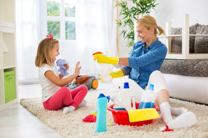 Reinigungshaus und -c$spielen der Mutter und des kleinen Mädchens stockbild