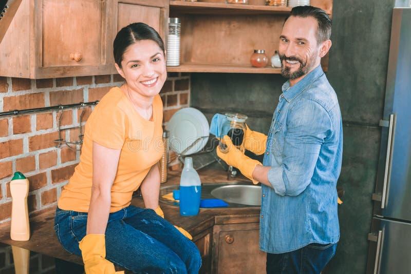 Reinigungsküche der frohen Paare mit Vergnügen lizenzfreie stockbilder