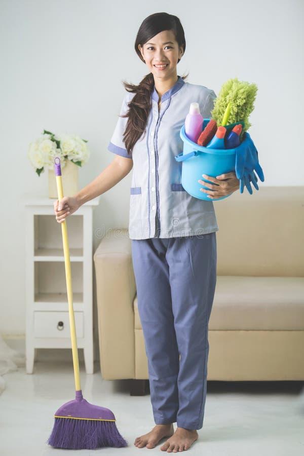 Reinigungsmädchenfrau, die zur Kamera lächelt lizenzfreies stockbild