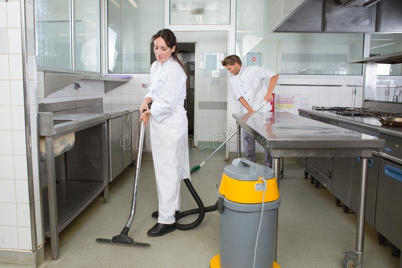 Reinigungsspülbecken mit zwei Hausmeistern mit Spray und Schwamm lizenzfreie stockfotografie