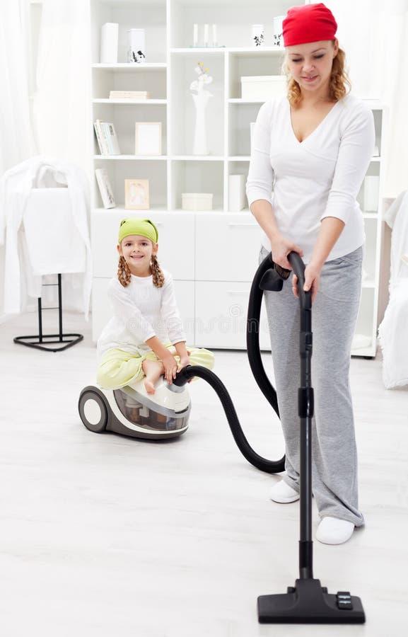 Reinigungstag - Frau und kleines Mädchen ordnen den Raum stockbild