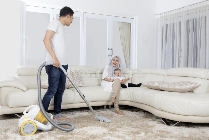 Reinigungsteppich des jungen Mannes mit Staubsauger lizenzfreies stockfoto