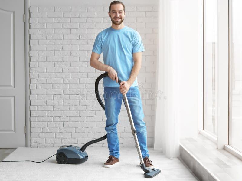 Reinigungsteppich des jungen Mannes mit Vakuum stockfotos