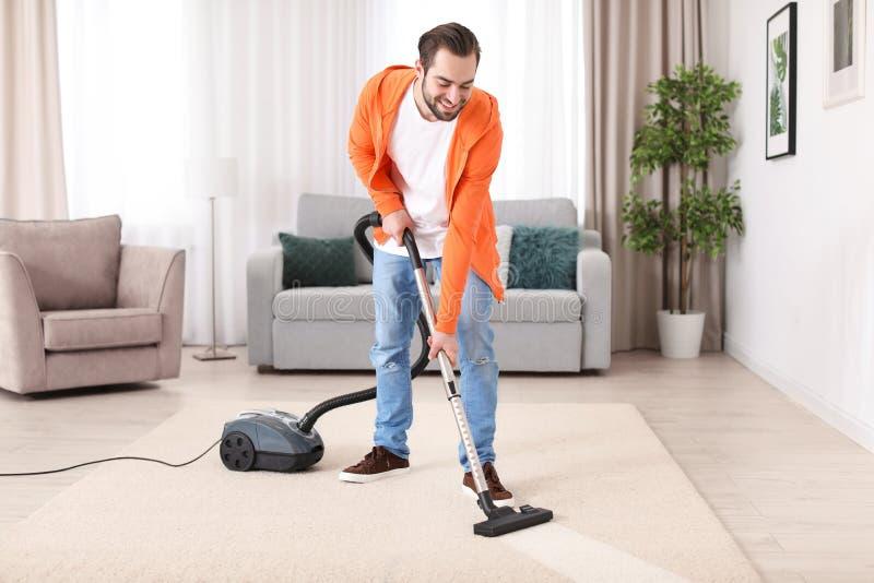 Reinigungsteppich des jungen Mannes mit Vakuum stockfoto