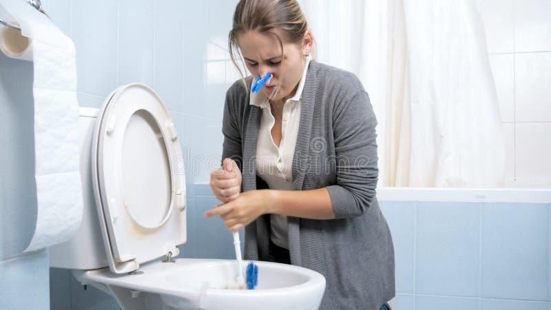 Reinigungstoilette der jungen Frau und das Versuchen zu erhalten reinigten weg vom schlechten Geruch lizenzfreie stockfotografie