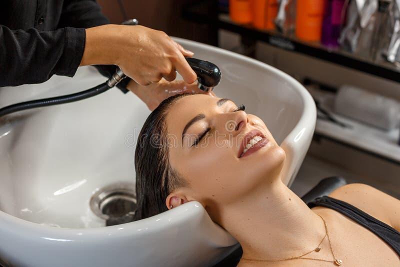 Reinigungsverfahren Schöne junge Frau mit waschendem Kopf des Friseurs am Friseursalon lizenzfreies stockfoto