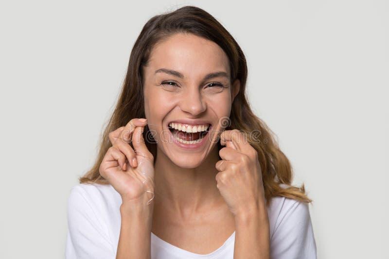 Reinigungszähne der glücklichen attraktiven Frau des Porträts mit Zahnseide stockfotografie