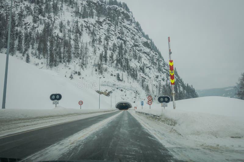 Reinli, Norvège - 26 mars 2018 : Vue extérieure de neige et de glace de route d'hiver dans la forêt, avec le signe instructif au photo libre de droits