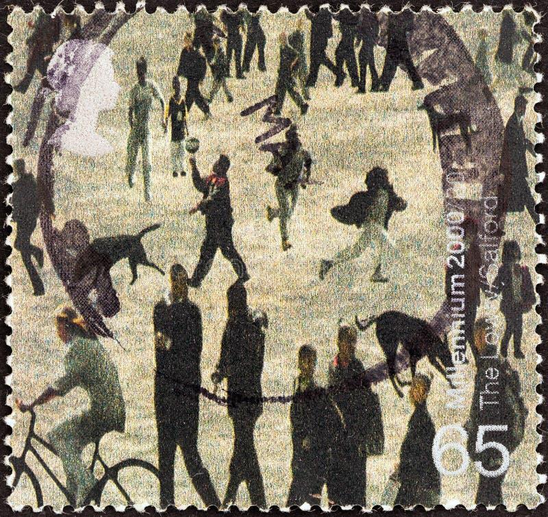 REINO UNIDO - CERCA DE 2000: Um selo impresso em povos das mostras de Reino Unido do centro de Salford Lowry, Salford, cerca de 2 fotos de stock