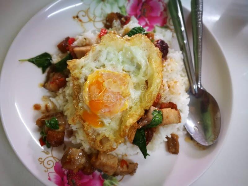 Reis überstieg Ei mit Aufruhr gebratenen Rindfleisch- und Basilikumthailand-streetfoods lizenzfreies stockfoto