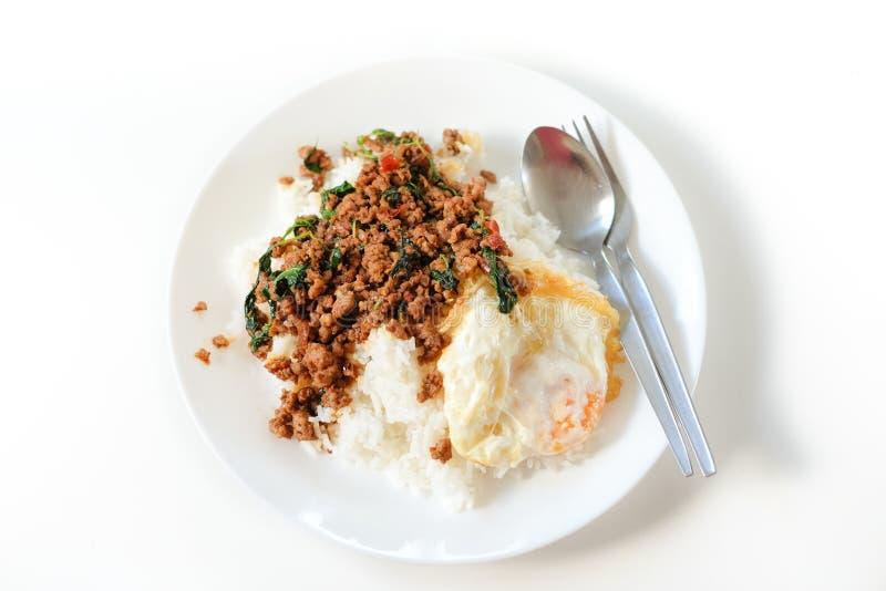 Reis überstieg mit angebratenem Schweinefleisch und Basilikumaufschlag mit Spiegelei stockfotos