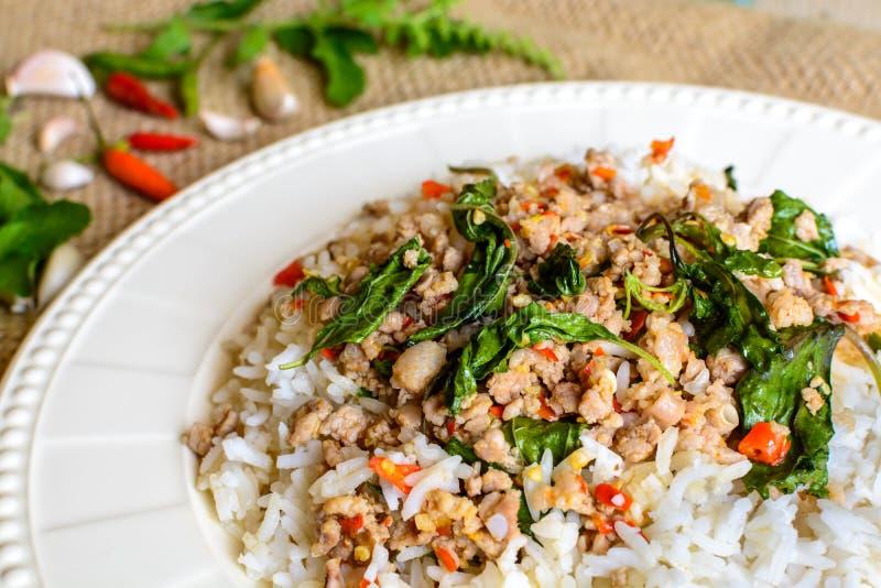 Reis überstiegen mit angebratenem Schweinefleisch und Basilikum lizenzfreie stockbilder