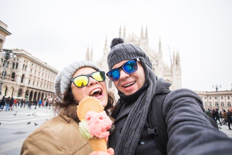 Reis in de winterconcept - Jonge en gelukkige toerist die selfie foto voor de beroemde Duomo-kathedraal in Milaan maken stock afbeelding