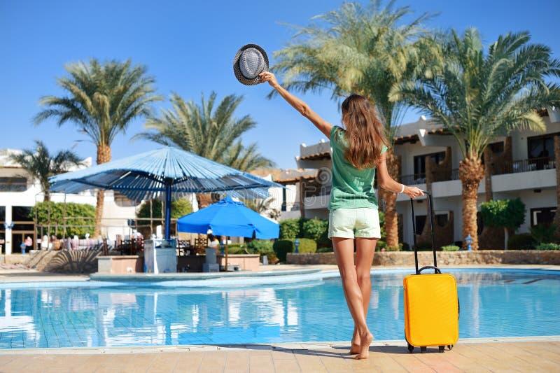 Reis, de zomervakantie en vakantieconcept - Mooie vrouw die dichtbij het gebied van de hotelpool met gele koffer in Egypte lopen stock fotografie