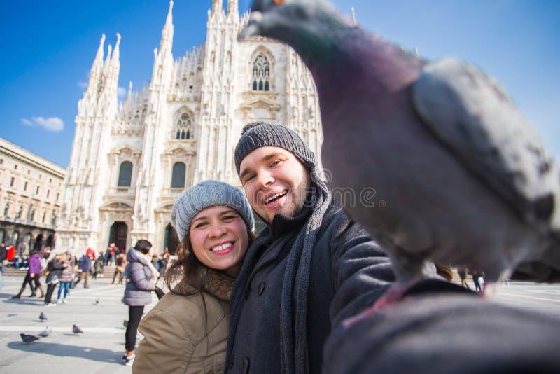 Reis, Itali? en grappig paarconcept - Gelukkige toeristen die een zelfportret met duiven voor Duomo-kathedraal nemen stock foto's