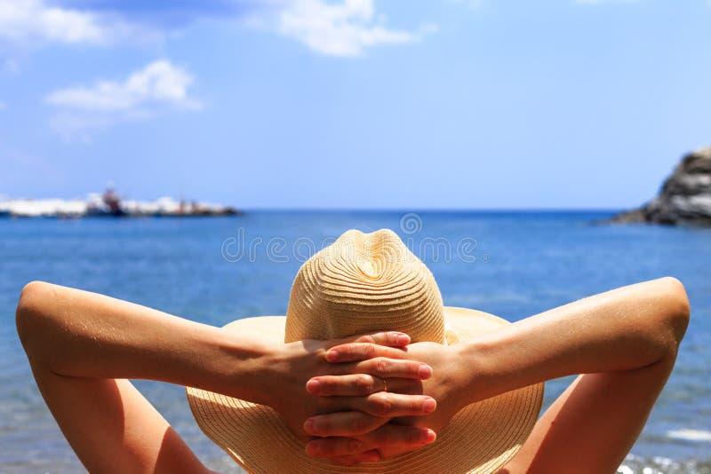Reis, roeping, vakantieconcept De vrouw in hoed ligt op deckchair op strand door overzees stock foto's