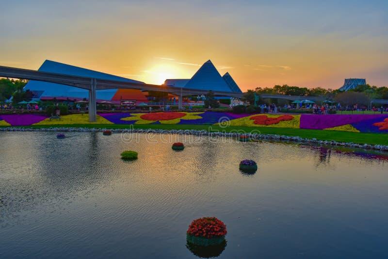 Reis in verbeeldingsaantrekkelijkheid, monorailweg, kleurrijke cijfers van mickey met bloemen en meer op mooie zonsondergang back stock afbeelding