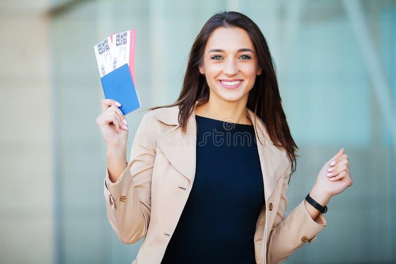 Reis Vrouw die twee luchtkaartje in in het buitenland paspoort houden dichtbij luchthaven royalty-vrije stock fotografie