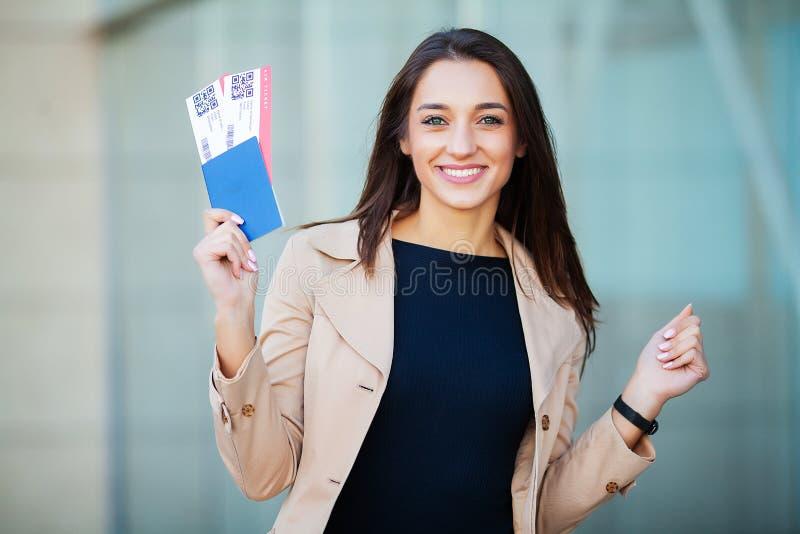 Reis Vrouw die twee luchtkaartje in in het buitenland paspoort houden dichtbij luchthaven royalty-vrije stock afbeeldingen