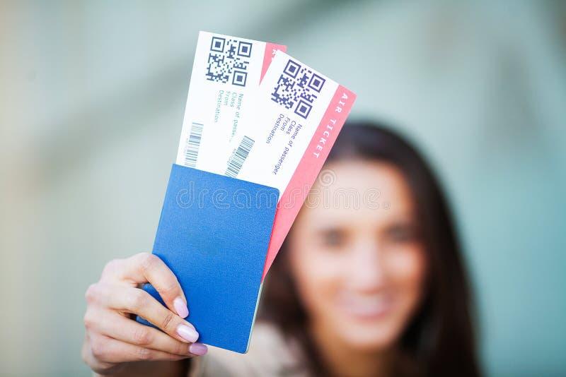 Reis Vrouw die twee luchtkaartje in in het buitenland paspoort houden dichtbij luchthaven stock fotografie
