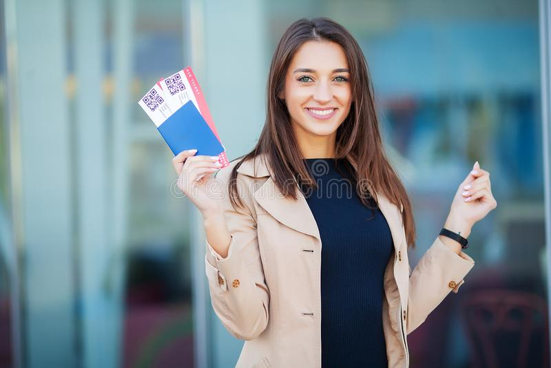 Reis Vrouw die twee luchtkaartje in in het buitenland paspoort houden dichtbij luchthaven royalty-vrije stock afbeelding