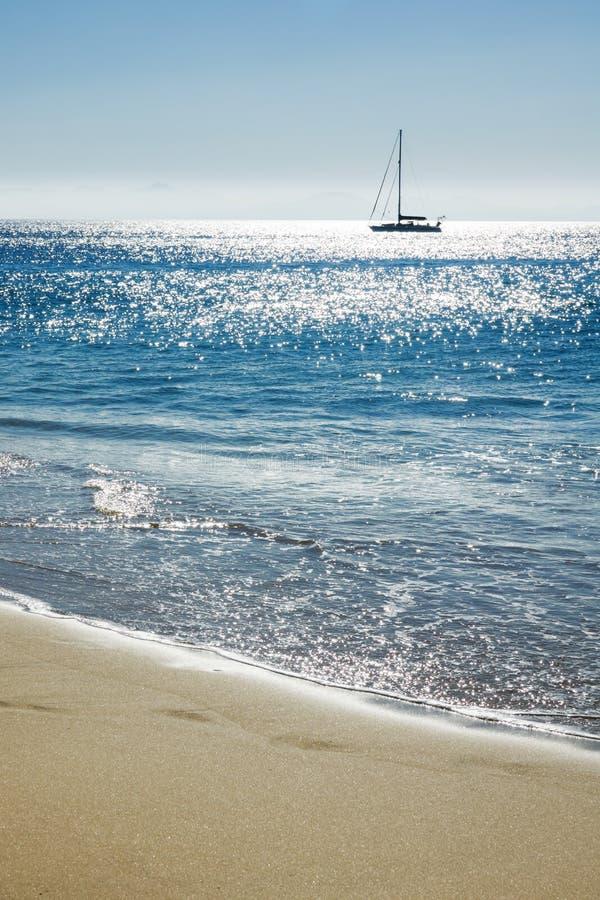 Reisachtergrond met zand van het strand, het blauwe overzees en het silhouet van een varende boot stock afbeeldingen