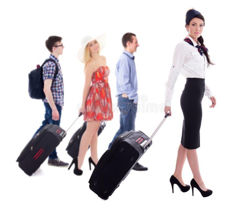 Reisconcept - zijaanzicht van stewardess en toeristen met suitc stock fotografie
