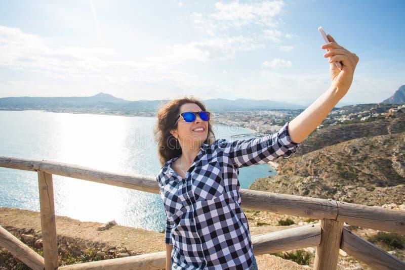 Reise-, Ferien- und Feiertagskonzept - junge Frau, die den Spaß, selfie, verrücktes emotionales Gesicht und das Lachen nehmend ha stockfoto