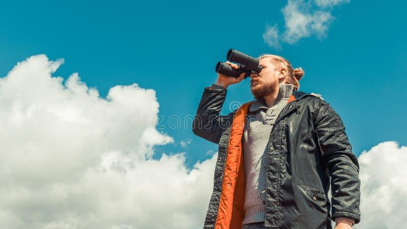 Reise-Suchpfadfinder Concept Starker Reisend-Mann, der durch Ferngläser im Abstands-Überblick-Himmel schaut Niedriger Winkel-Punk lizenzfreies stockbild