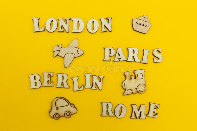 Reise um Europa, die Namen von Städten: 'Paris, London, Berlin, Rom 'auf einem gelben Hintergrund Hölzerne Zahlen eines Flugzeuge stockfotos