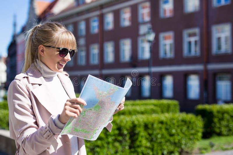 Reise- und Ferienkonzept - Tourist der jungen Frau, der die Karte betrachtet lizenzfreies stockfoto