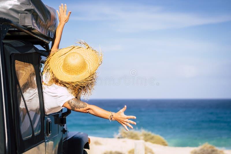 Reise- und Freiheitskonzept mit Freude und Freude - Menschen im Sommerurlaub - Frau außerhalb des Autos vor einem malerischen Ort stockfotografie