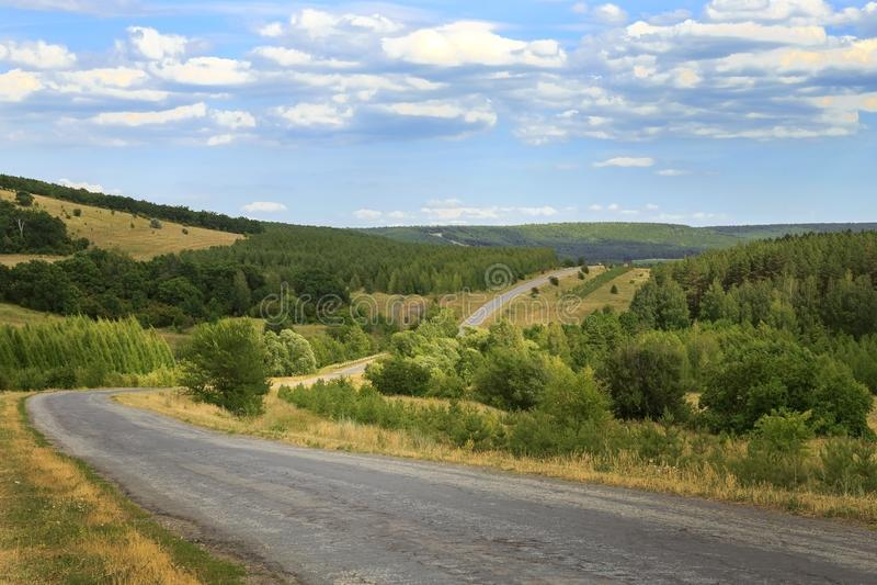 Reise und Tourismus Landschaft, Straße, die in den Abstand unter schönen grünen Wäldern ausdehnen und Hügel an einem Sommertag im stockbild