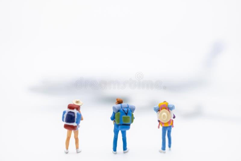 Reise-und Transport-Konzept Schließen Sie oben von der Gruppe der Reisendminiaturzahl mit Rucksackstellung auf weißem Hintergrund stockbild