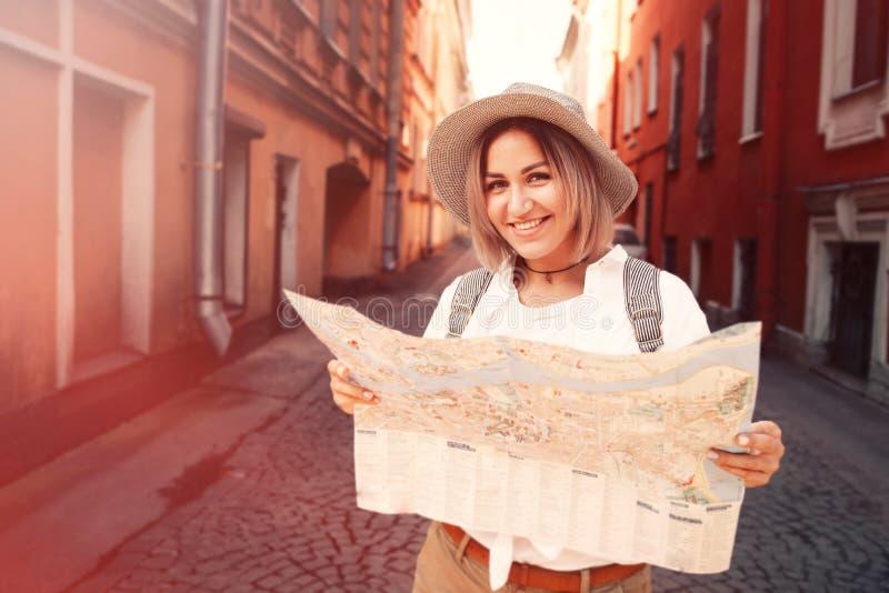 Reiseführer Junger weiblicher Reisender mit Rucksack und mit Karte auf der Straße kleines Auto auf Dublin-Stadtkarte stockfotografie