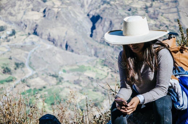 Reisefrau, die auf einem Felsen mit dem Hintergrund der Stadt von Canta sitzt lizenzfreie stockfotografie