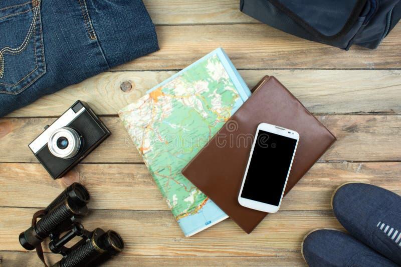 Reisekonzept auf Holztisch Draufsichtbild des Reisezubehörs mit gewaschenem heraus Weinlesefiltereffekt stockfotografie