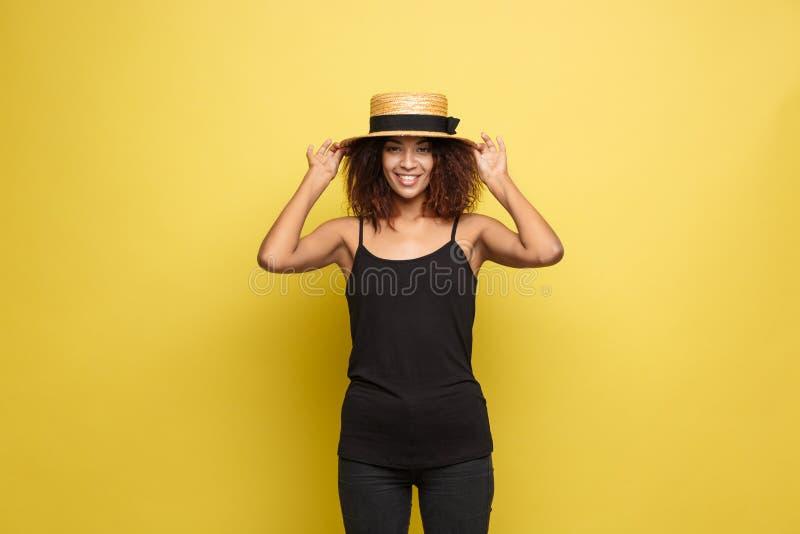 Reisekonzept - nahes hohes Porträt-junge schöne attraktive Afroamerikanerfrau mit modischem Hut lächelnd und froh stockfoto
