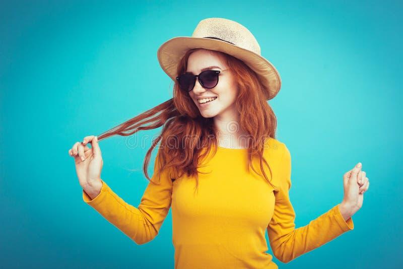 Reisekonzept - nahes hohes Porträt junges schönes attraktives redhair Mädchen mit dem modischen Hut- und sunglasslächeln blau stockfotos