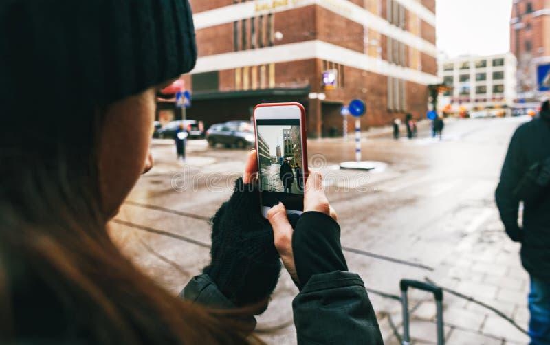Reiselebensstilfrau, die Bildfreundstraßen-Stockholm-Winter nimmt lizenzfreies stockbild