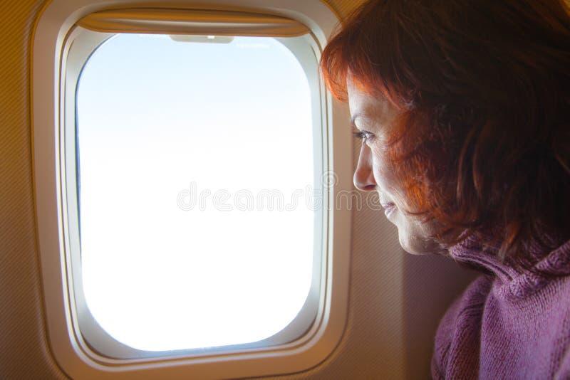 reisen Frau sitzt im Flugzeug lizenzfreie stockfotos