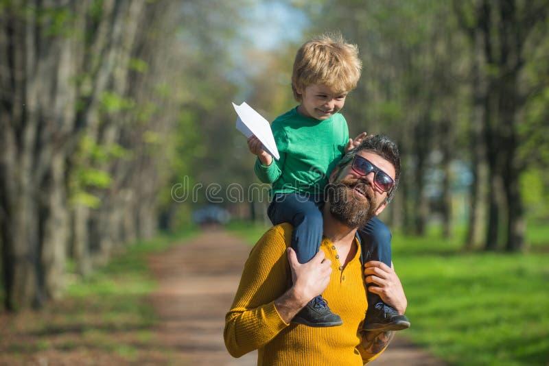 Reisen mit dem Flugzeug Kleiner Kinderjunge auf Vätern schultern Produkteinführungspapierfläche im Park, reisendes Konzept Besser lizenzfreies stockbild