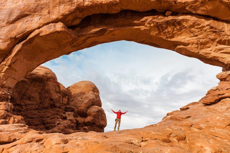 Reisen Sie in Bogen-Nationalpark, Mannwanderer mit Rucksack im Nordfenster, Utah, USA stockfotografie