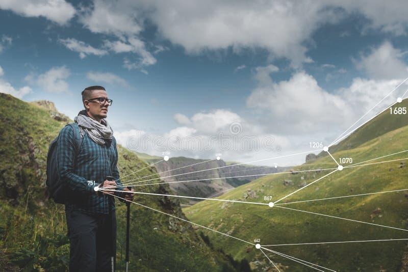 Reisend-Mann mit Rucksack und Wanderstöcken setzt vergrößerte Wirklichkeitstechnologie in der Reise ein lizenzfreies stockfoto
